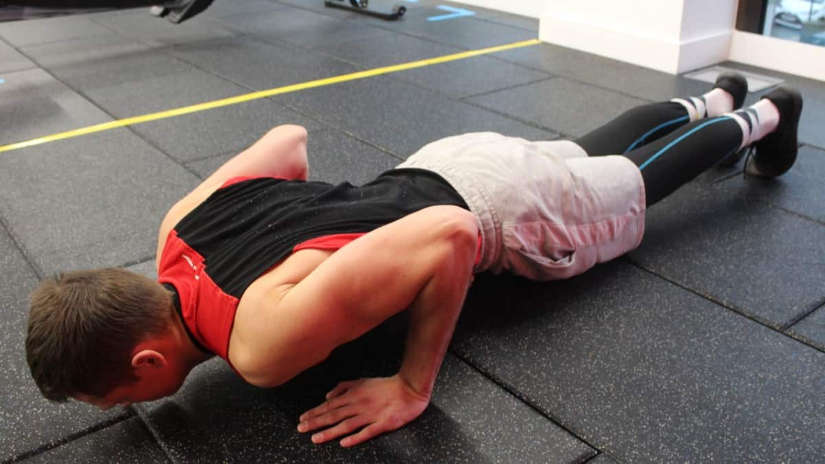 Mike in dipping down during the second step of performing the standard proper pushup form.