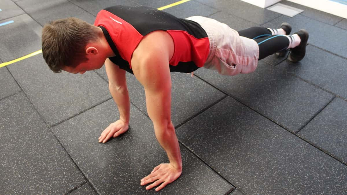 Mike in the plank position during the first step of performing the standard proper pushup form.